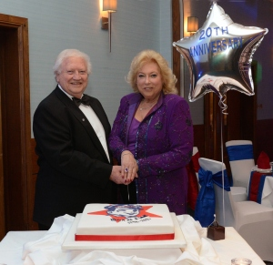 Jan and Freddie Mitman cut a cake to celebrate Drain Doctor's 20th anniversary.