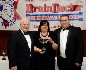 Michelle and Stuart Brock receive their growth award from Drain Doctor Plumbing chairman Freddie Mitman (left).